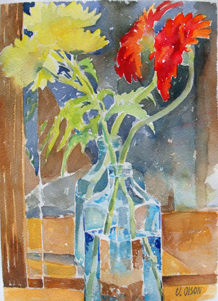 A watercolor of large red and yellow petalled flowers in a clear blue glass vodca bottle three quarters filled with water reflected int the mirror of a closet.