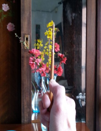 First I measure the vase against the flowers to see how many times the vase fits into the flowers.