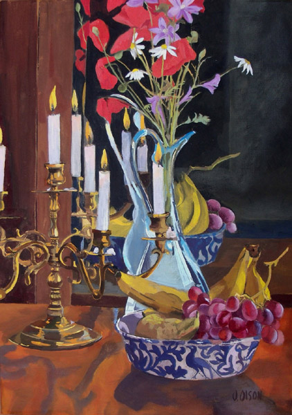 Egg tempera painting of evening scene with candalabra, glass ewer with a blue leaf design with bananas, red grapes and a pear. In the ewer there are Spanish wild flowers poppies, purple flowers and daisies all reflected in the mirror.
