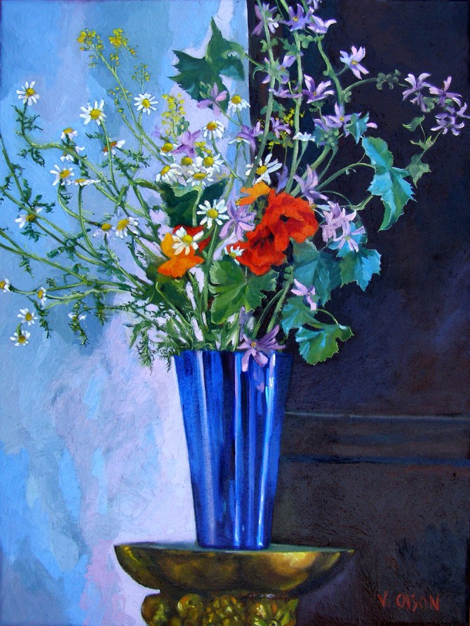 Large oil painting with brightly colored yet naturalistic colors and shapes of Spanish wild flowers, deep orange..red poppies, little purple pettaled flowers and white daisies with a large yellow circle in the middle in a cobolt blue flower vase on top a a high stand guilded in gold against a white wall and wood panel.