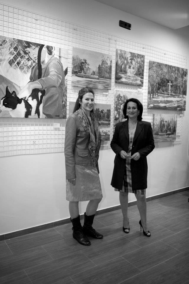 Two young woman at their painting exhibition in front of paintings