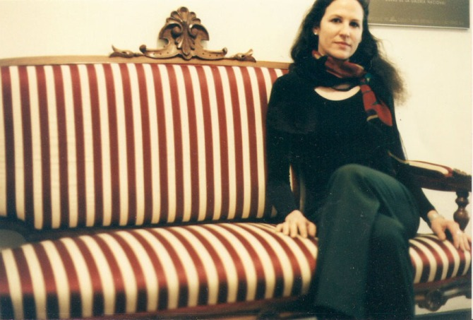 Young woman sitting on striped couch.