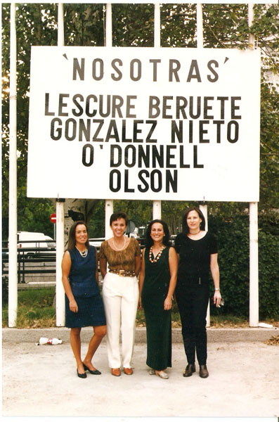 Four young women standing in front of a billboard with their names on it.