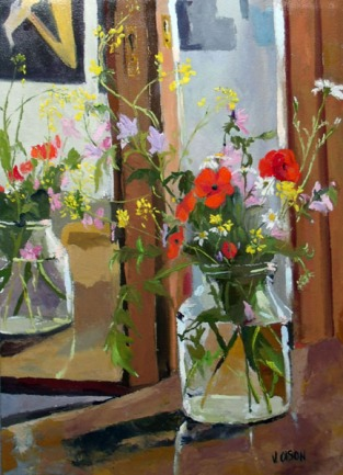Poppies and wild purple, violet and yellow flowers in a pickle jar reflected in the mirror.