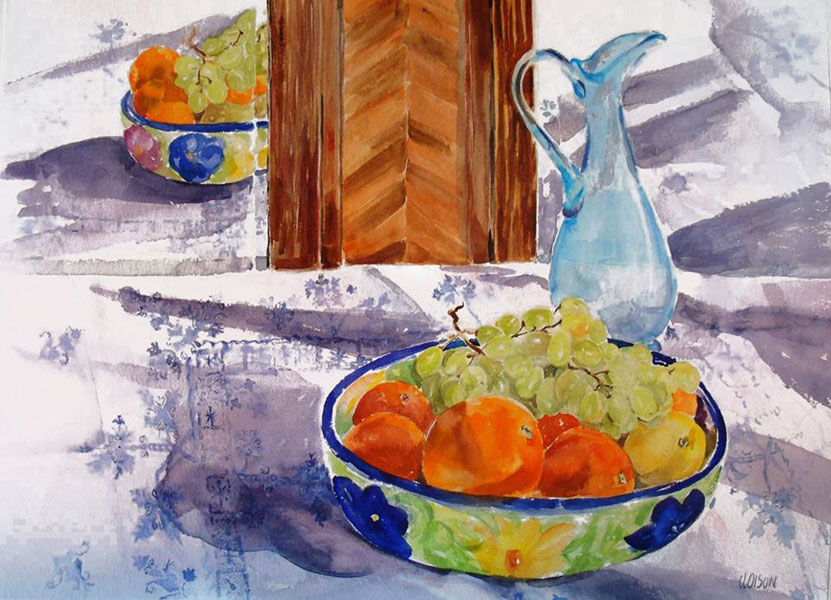 A large watercolor of a fruit bowl full of tengerines and grapes over a white table cloth with blule print. There is a blue glass ewer also and all reflected in the mirror.