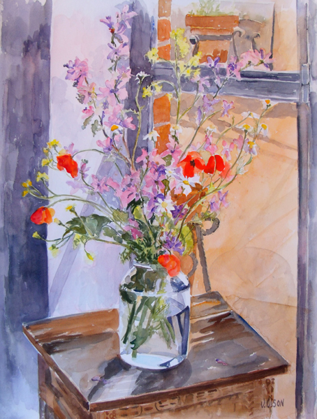 Poppies and wildflowers in pickle jar on top on little wooden table in front of a window.