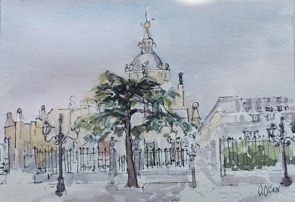 A small watercolor of the Almudena Cathedral. Blue sky with a bit of crimson. The Almudena has a huge evergreen growing in front of the gate. There are a few street lamps with the black latern from days of old. The view is from accross the street.