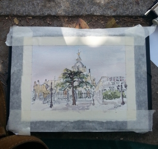 A small watercolor of the Almudena taped down to a drawing board. There is a big evergreen in front of the gate. The Almudena is seen from accross the street.
