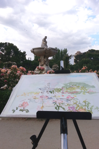 A picture of a watercolor in process in the Rose Garden. Easel and paper in front of the fountain.