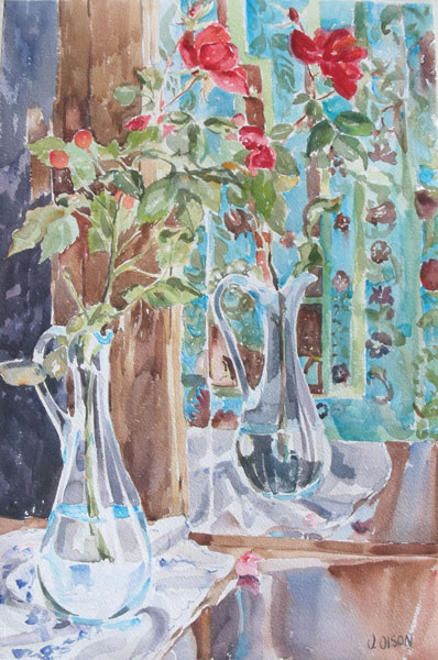 A watercolor of a clear glass blue ewer with red roses reflecting in mirror. The almost half filled ewer is sitting on top of a white tablecloth and there is a blue background since there is a blue patterned curtain reflecting in the mirror too.