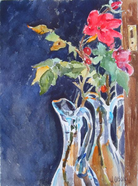 A watercolor of a red rose and a few buds reflected in the mirror. There is also an ewer made of clear blue glass, The background is a dark blue almost a black blue.