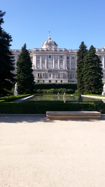 A photo of the Royal Palace from the Sabatini Gardens. Can see the Royal Palace with a little dome on top and tall evergreens in the foreground, four trees are visible. The pond has three square fountains with water shooting up.