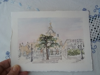 A small watercolor of the Almudena in my hand to see the size. You can see a thumb holding a corner of the watercolor. The watercolor is a line and wash of the Almudena Cathedral with a big evergreen in front of the main gate. You can also see some old time street gas lamps.
