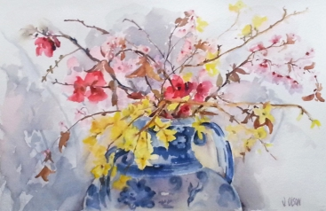 A watercolor of Spanish Spring yellow and pink flowers in a Talavera vase with two handles although in the painting you can only see one. The backround is against a white wall with the shadows casting the shapes and forms of the flowers and reflecting purples, violets and pinks enveloped in grey.