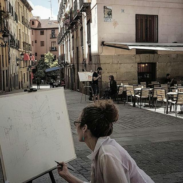 A photograph of me with a pen and ink drawing on an easel in Madrid's Plaza del Conde de Barajas.