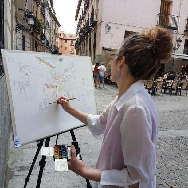 A photo of a woman painting a street in Madrid on site.