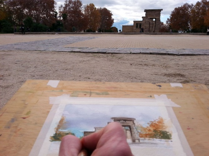 This is a picture of a person painting a watercolor of the Temple of Debod. You can see the hand painting and the model which is Debod Temple.