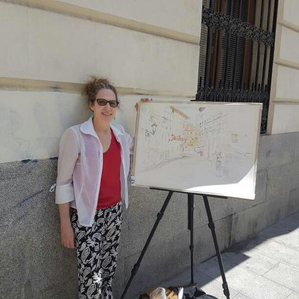 A woman standing next to an easel with the start of a watercolor.