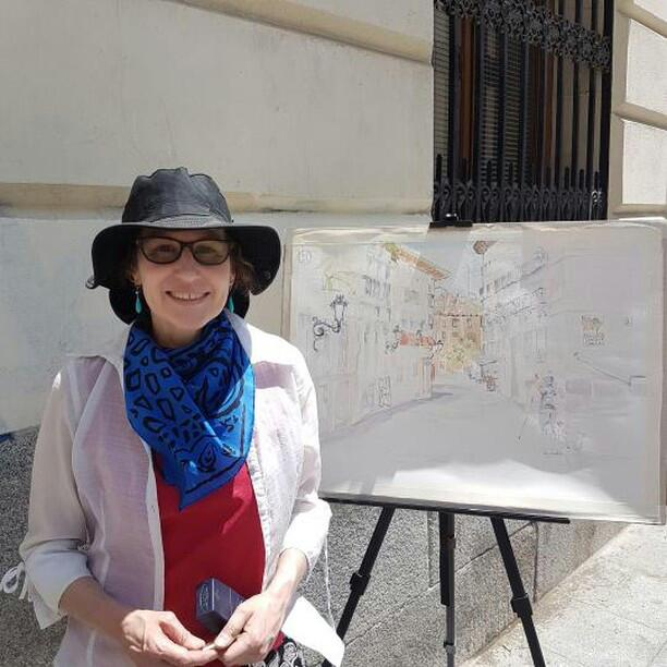Woman standing in front of easel with started watercolor wearing watercolor gear, hat, scarf and long sleeve white shirt and tinted glasses.