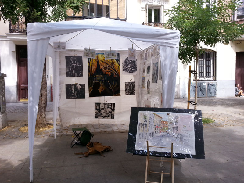 A white tent at Plaza de los Pintores with watercolors, prints and oil paintings