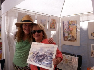 Two ladies standing under a white tent with watercolors.