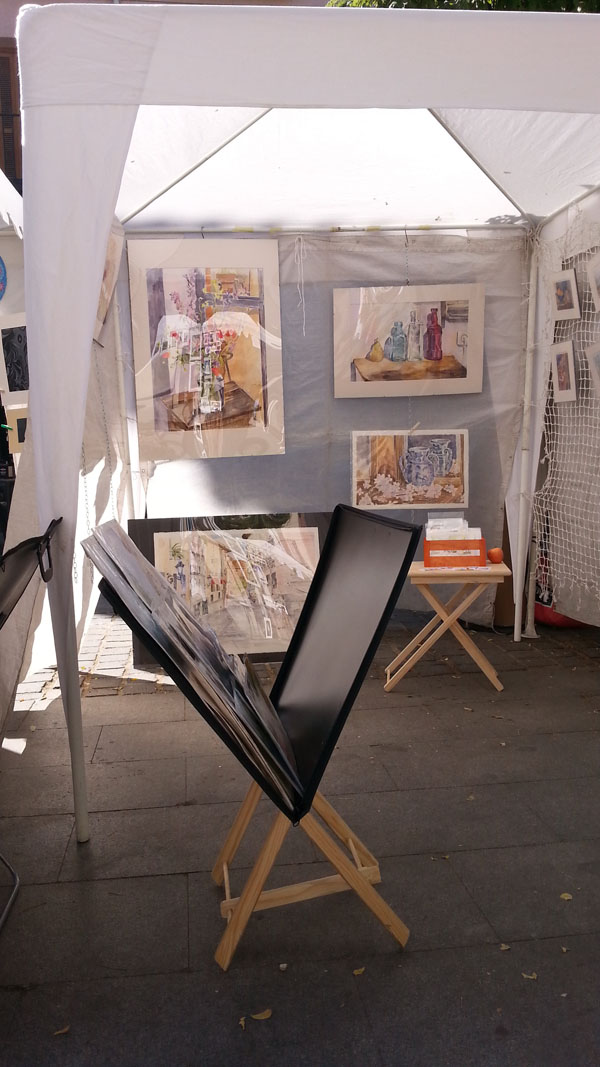 Art stand with watercolors hanging and a portfolio in the foreground
