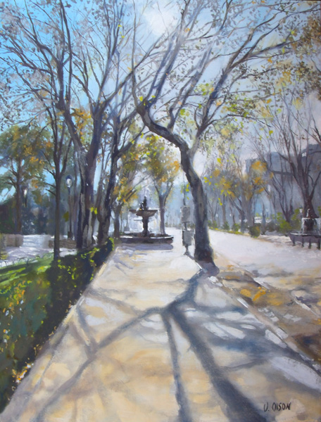 A painting of the Paseo del Prado in Madrid Spain. Autumn leaves of yellow, orange and green against a clear blue sky. The afternoon light casts a shadow on the trees on the side walk. You can see the main road without any cars. There is a fountain in the middle of the walk way lined by trees.