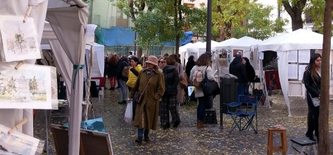 Art stands in the fall in Madrid. People walking around looking at the art exhibition in the little plaza