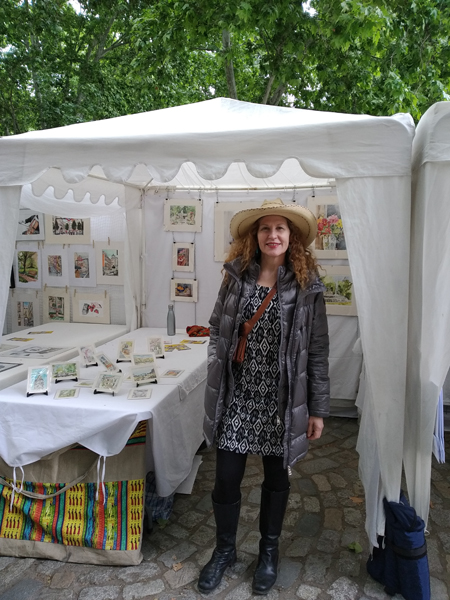 Lady with Hat standing in front of her art stand.