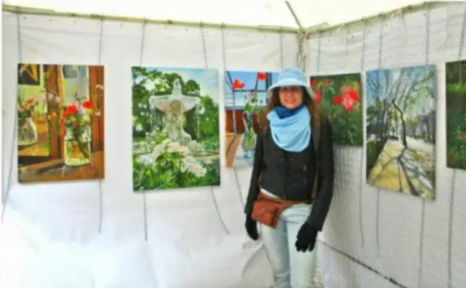 Art stand with female artist with blue hat and blue scarf.