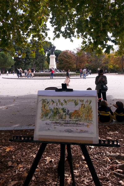 A Watercolor of the Fallen Angel Fountain in the autumn. The watercolor is on an easel and the fountain is in the background