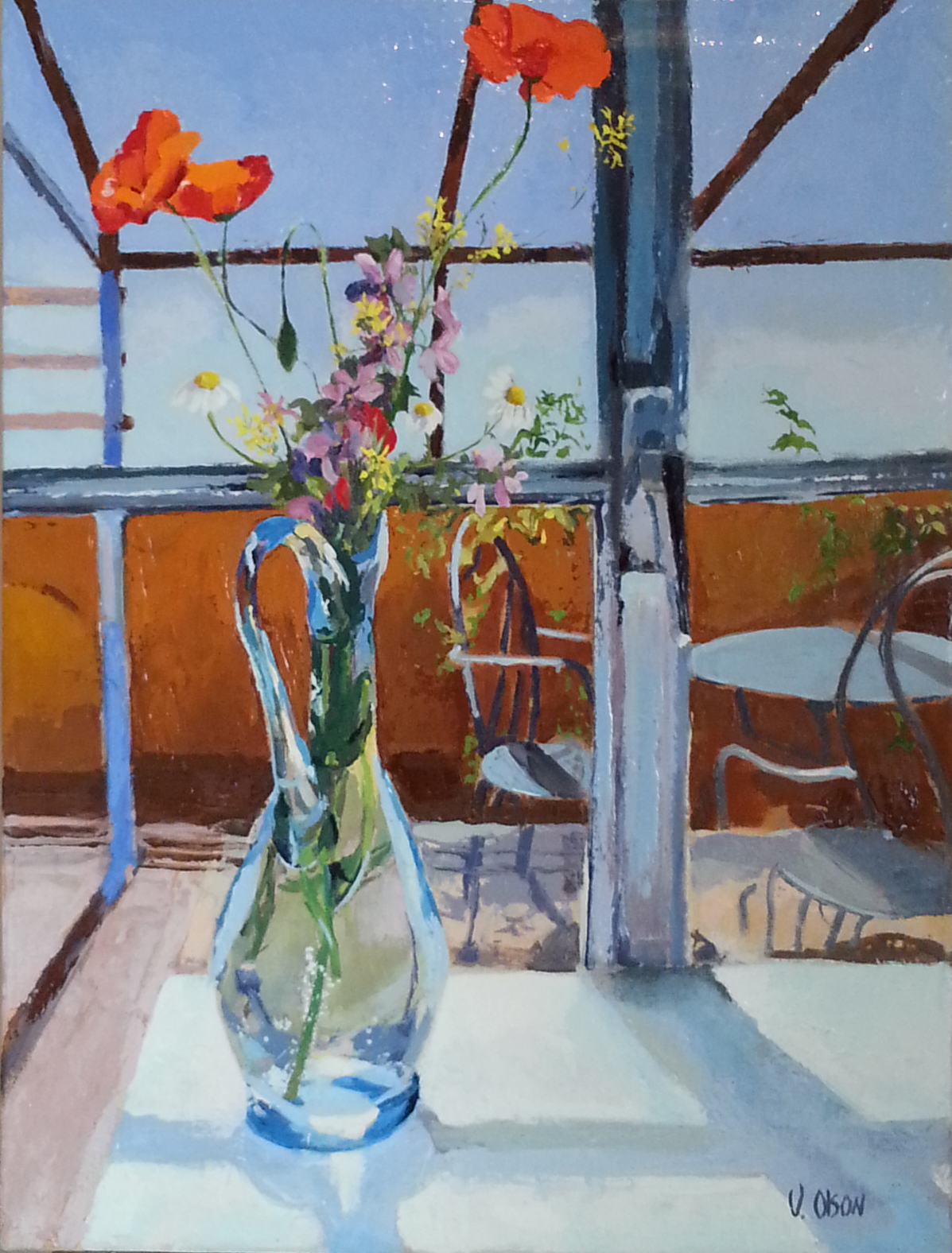 Red Poppies and Wild Flowers in a glass blue Ewer. The Ewer is sitting on a white table in front of a window door
